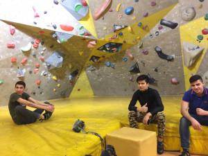 Unbegleitete minderjährige Flüchtlinge sitzend in einer Boulder-Halle.