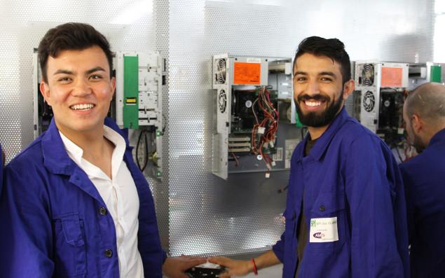 Zwei Teilnehmer einer Berufsausbildung vor elektrotechnischen Anlagen