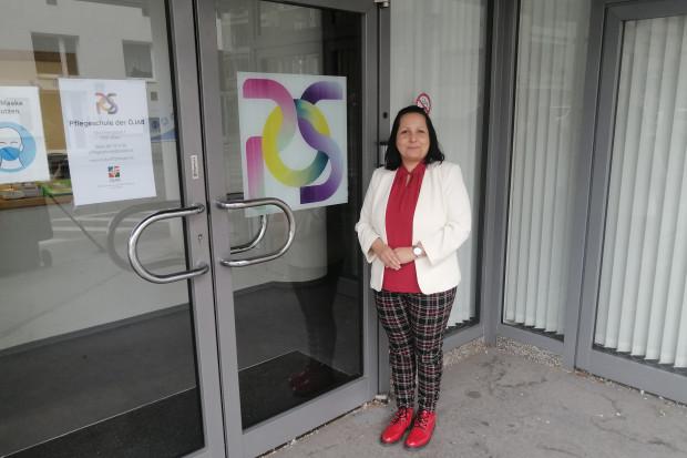 Lehrgangsleiterin Lenka Slepčíková vor dem Eingang der Pflegeschule der ÖJAB.