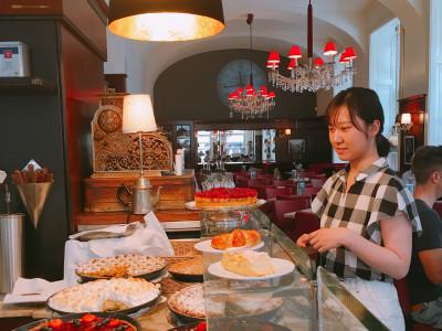 Japanische Reiseteilnehmerin vor einer Auswahl an Kuchen in einem Wiener Kaffeehaus. Foto: Momoko Morisaki.
