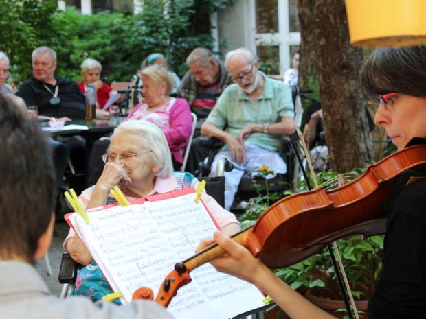BewohnerInnen sitzend vor MusikerInnen im Garten des Hauses.