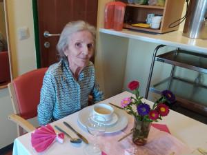 Lächelnde Bewohnerin am gedeckten Tisch beim Essen
