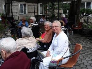 BewohnerInnen und Angehörige sitzend  bei einem Gartenkonzert im ÖJAB-Haus Neumargareten.