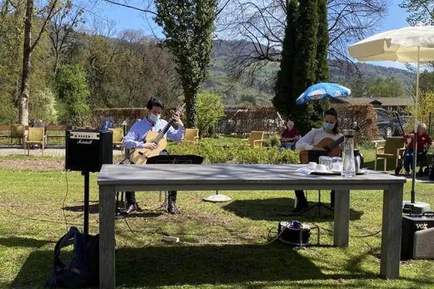 Musikstudierende Antonia Haslinger und Panagiotis Tzortzis bei ihrem Konzert für die BewohnerInnen der ÖJAB-SeniorInnenwohnanalage Aigen im Garten des Hauses.
