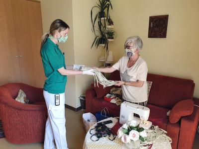 Danke! Die Bewohnerin übergibt der Pflegerin die fertigen Schutzmasken als Dankeschön für den Einsatz.