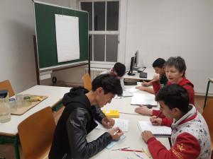 Unbegleitete minderjährige Flüchtlinge beim Unterricht im Klassenzimmer mit Lehrerin.