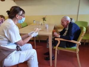 Pflegerin spielt Karten mit Bewohnerin
