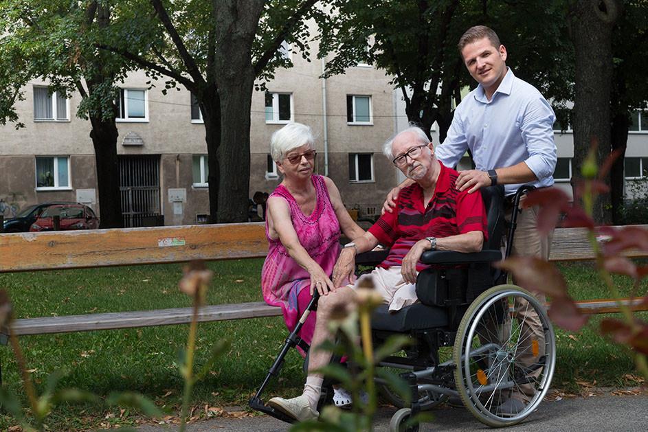 Symbolbild Pfleger mit Klienten und Angehöriger beim Spaziergang im Park.