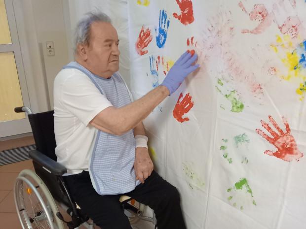 Senior hinterlässt bunte Händeabdrücke auf einem Plakat.
