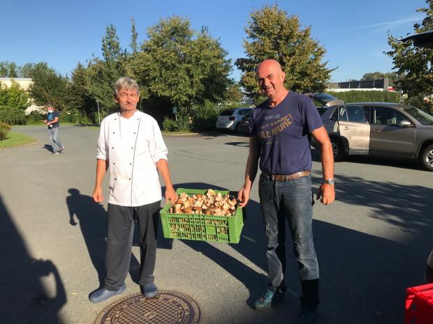 Karl Krammer vom ÖJAB Haus St Franziskus übergibt Küchenchef Jürgen Minixhofer Schwammerl für die BewohnerInnen.