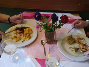BewohnerInnen beim Essen, Speisen in Großaufnahme auf dem dekorierten Tisch.