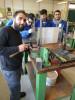 Foto 1: Grundlagenunterricht für MANA-TeilnehmerInnen in der Mechanischen Werkstätte an der HTL Mödling. Eine Metallwerkstück wird nach dem auf dem Glas montierten Plan bearbeitet.