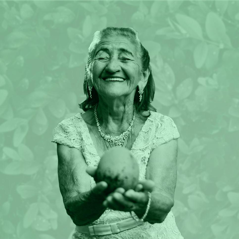 Symbolbild alte Dame hält Stein und lächelt.