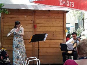 Nahaufnahme der Musikerin Marcela Lechtova an der Flöte und Romero Tizoc an der Gitarre im Garten des Wohn- und Pflegewohnheims.