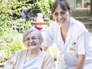 Bewohnerin und Pflegerin gemeinsam im Garten des ÖJAB-Hauses Neumargareten.