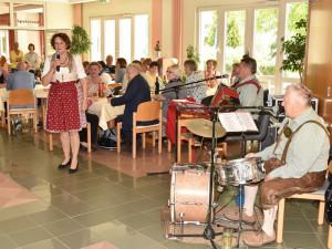 Heim- und Pflegedienstleiterin Elisabeth Muhr stehend mit Blasmusikkapelle.