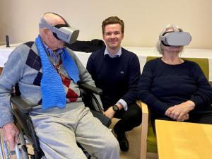 BewohnerInnen sitzend mit aufgesetzter VR-Brille. Heimleiter Patrick Ebeling knieend.