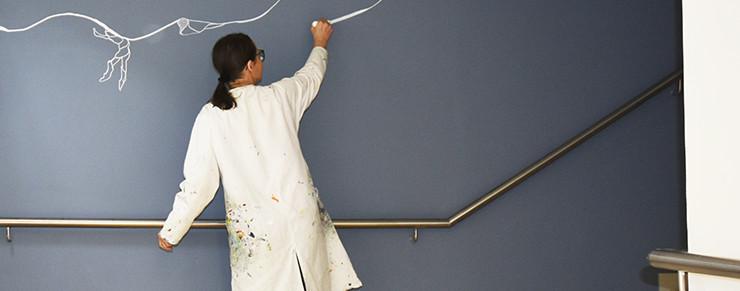 Künstlerin Birgit Schweiger bei der Anfertigung einer Wandzeichnung im Stiegenhaus des Hauses.