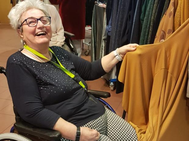 BewohnerInnen sitzend vor einem Kleiderständer des mobilen Modeverkaufs in der ÖJAB-SeniorInnenwohnanlage Aigen.