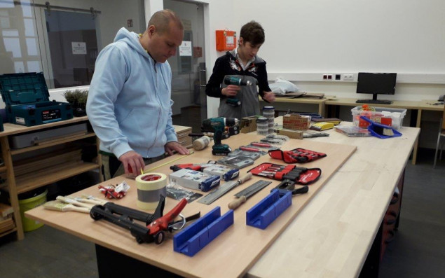 Teacher and apprentice standing in front of a workbench with tools.