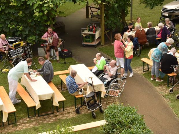 Aufnahme des Grillfestes von oben, BewohnerInnen und MusikerInnen sitzend und BewohnerInnen tanzend.