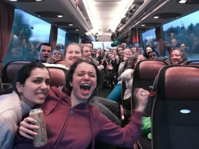 Participants of the ÖJAB ski excursion having fun in the bus bringing them to a ski resort.