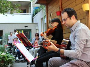 Nahaufnahme der Musikerin Irene Malizia an der Violine und Angelos Tatone an der Gitarre im Garten des Wohn- und Pflegewohnheims.