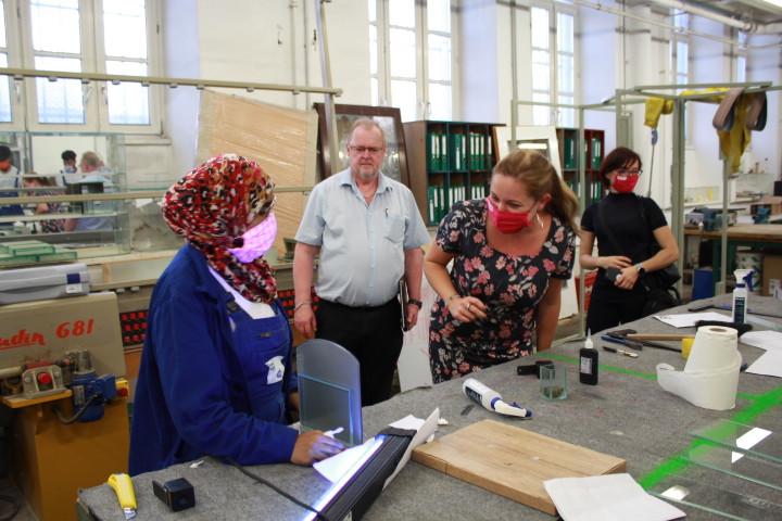Eine Auszubildende aus dem Bereich Glasbautechnik zeigt Nicole Meissner ihr erlerntes Können.