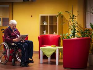 Resident sitting in the foyer of the ÖJAB SeniorInnenwohnanlage Aigen.