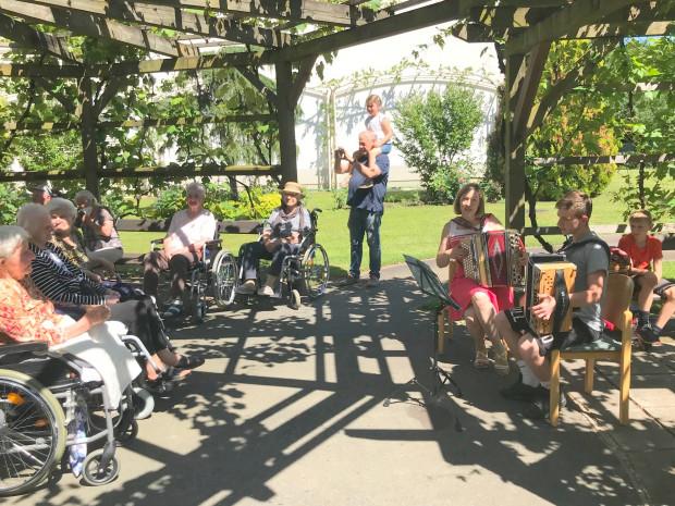 BewohnerInnen und MusikerInnen im Garten des ÖJAB-Hauses St.Franziskus.