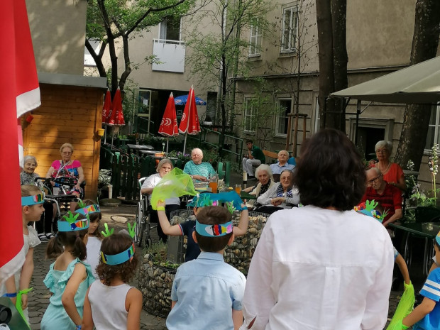 Kinder des hauseigenen Kindergartens bei einer Tanzaufführung im Garten für BewohnerInnen des ÖJAB-Hauses Neumargareten.