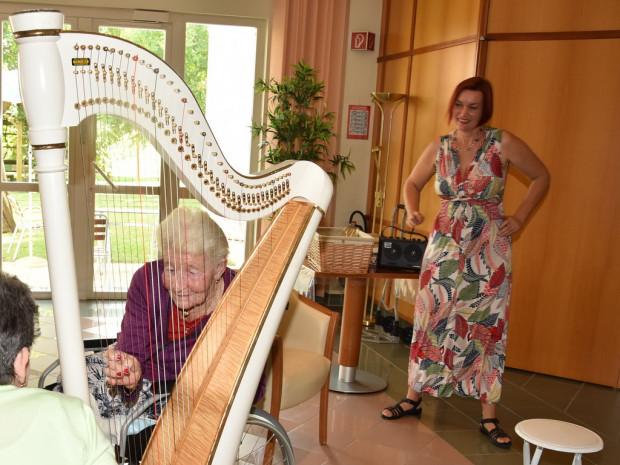 BewohnerInnen des Pflegewohnhauses ÖJAB-Haus St. Franziskus sitzend an der Harfe und Musikerin Sabine James stehend im Hintegrund.
