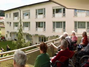 BewohnerInnen des ÖJAB-Hauses St. Franziskus am Balkon sitzend und dem Konzert im Garten lauschend.
