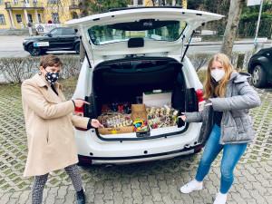 Zwei Projektteilnehmerinnen vor dem Auto, das mit den Ostergeschenken bepackt ist.