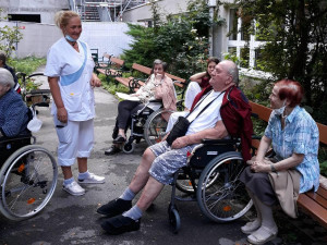 BewohnerInnen und Angehörige sitzend, neben Pflegemitarbeiterin stehend, bei einem Gartenkonzert im ÖJAB-Haus Neumargareten.