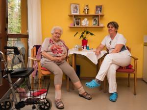 Nurse with resident sitting and having a chat at the ÖJAB SeniorInnenwohnanlage Aigen.