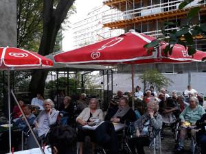 Musiker mit dem Rücken zur Kamera vor Publikum im Garten des Wohn- und Pflegewohnheims.