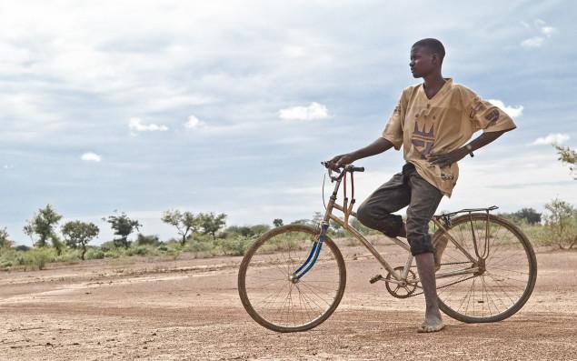 Junger Bewohner Burkina Fasos auf einem Fahrrad sitzend blickt nachdenklich in afrikanische Landschaft.