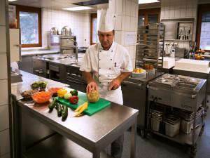 Employee of the  ÖJAB SeniorInnewohnanalage Aigen preparing food in the kitchen.