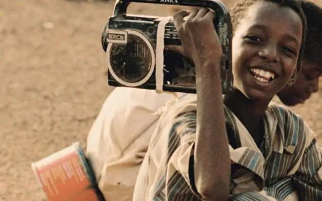 Symbolbild lächelndes afrikanisches Kind mit tragbarem Radio auf der Schulter im Vordergrund. Kind im Hintergrund sitzend.