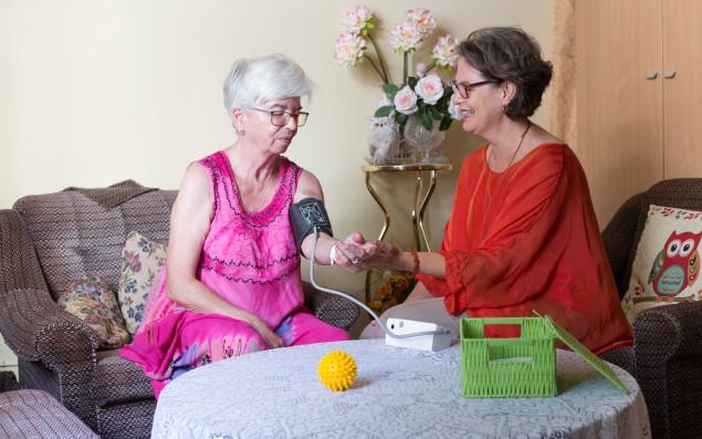 Pflegerin misst den Blutdruck einer Bewohnerin in Heimzimmer.
