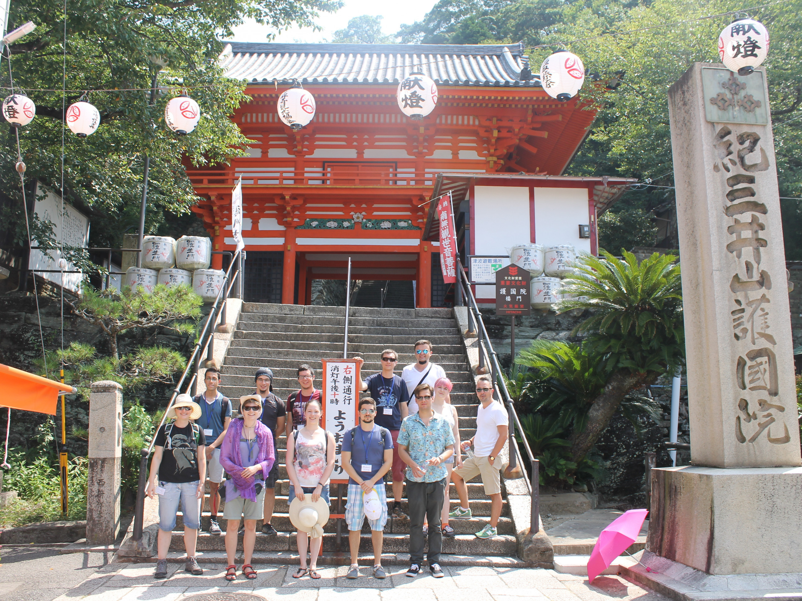 Teenagers from Austria in Japan. The group stands in front of a Japanese temple entrance.