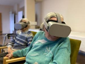 BewohnerInnen sitzend mit aufgesetzter VR-Brille.
