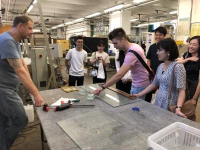 Fachtrainer zeigt japanischer Reise-Gruppe die Werkstätten des BPI in der Längenfeldgasse.