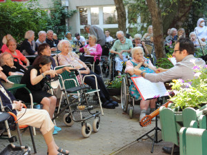 BewohnerInnen und Angehörige sitzend vor zwei MusikerInnen bei einem Gartenkonzert im ÖJAB-Haus Neumargareten.