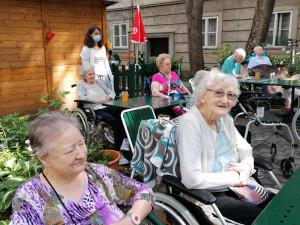 SeniorInnen sitzend im Garten des ÖJAB-Hauses Neumargareten genießen die Tanzaufführung der Kinder der kindercompany.