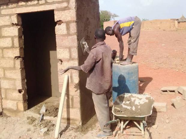 Two local Burkinabe craftsmen building a latrine in the Burkinabe community of Samba.