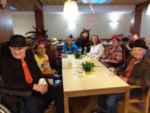 BewohnerInnen, MitarbeiterInnen und Angehörige gemeinsam am Tisch sitzend.