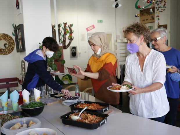 Jugendliche und TrainerInnen beim Zubereiten von Speisen.