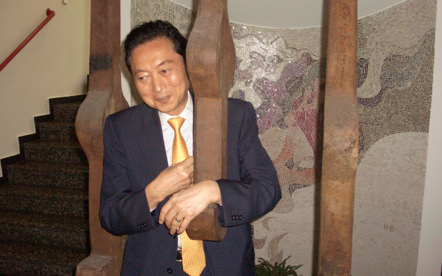 Photo of Yukio Hatoyama and Petra Heidler standing in a traditional Japanese room and shaking hands with each other.